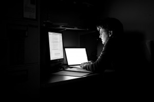Man at a desk in a dark room, lit by two computer monitors