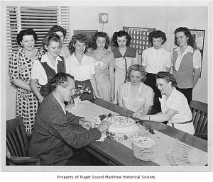 A group of women gather around a man cutting a birthday cake in a 1940s office